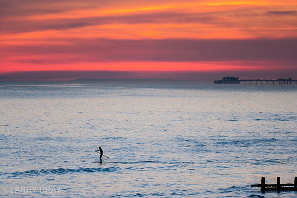 Paddle boarder  and Worthing Pier silhouetted in sunset from Shoreham-by-Sea, West Sussex, UK