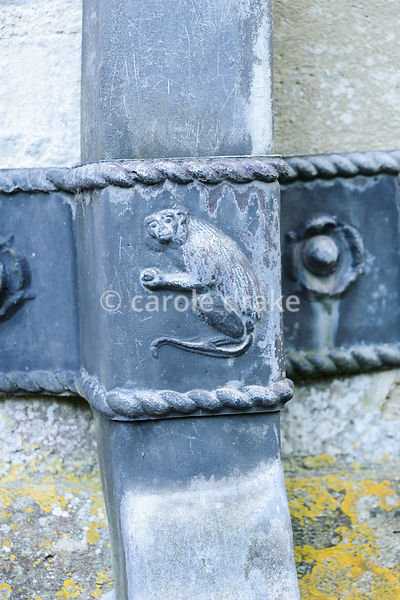 Decorative drain pipe fixing with image of a monkey. Rodmarton Manor, Rodmarton, Tetbury, Glos, UK