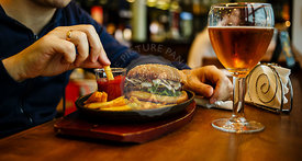 Burger with French fries in male hands and Beer on wooden table background