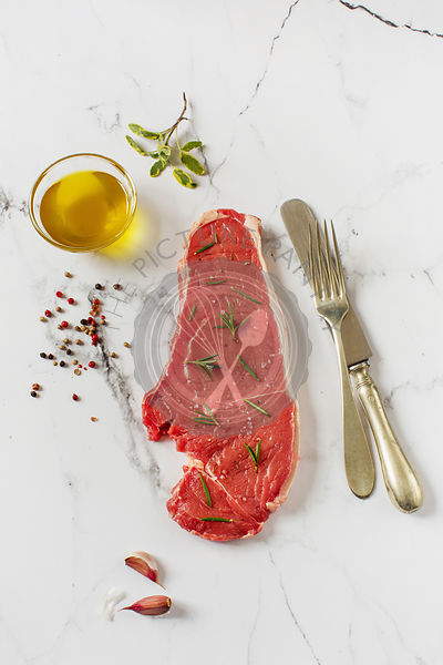 Raw beef steak on a white marble worktop