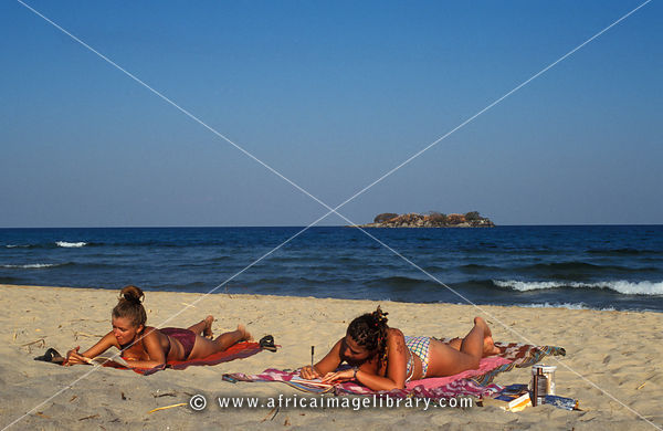 tourists sunbathing on the beach, Kande beach, Lake Malawi, Malawi