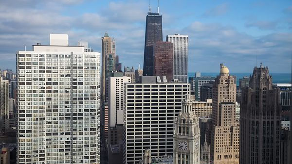 Bird's Eye: Medium Shot - Low Deck of Stratus Clouds Dragging Soft Shadows Across Skyscrapers of Chicago
