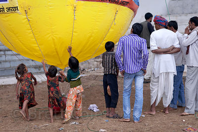 Children touch a hot air balloon in Pushkar, Rajasthan, India