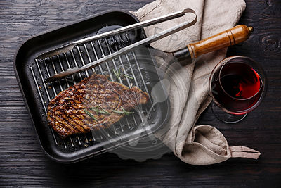 Grilled Steak Striploin in grill iron pan and red wine on black burned wooden background