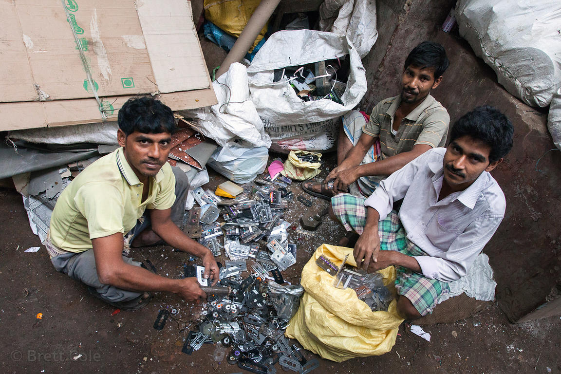 Men disassemble cassette tapes at a makeshift recycling facility in an old decaying building in the Shyambazar area of Kolkat...