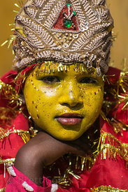 A girl in yellow makeup to pose for photos with tourists in Pushkar, Rajasthan, India