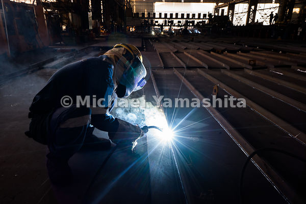 Sparks of white light illuminate the darkened room as a worker hunches over the floor, armed with a welding torch.