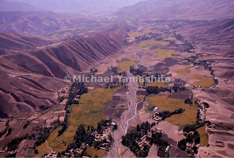 An aerial view of farmland surrounded by mountains in Feyzabad, Afghanistan.
