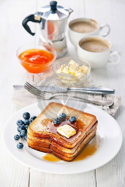French toast with blueberries, maple syrup and butter