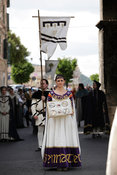 young maiden from one of the contradas of Narni in Umbria Italy in procession carrying silver rings awarded to winners on joust