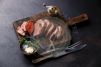 Sliced tenderloin Steak Roast beef with knife and fork carving set on wooden cutting board on dark background