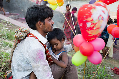 A man holds his son while selling balloons during immersion of Ganesh idols in the Yamuna River for the Ganesh Chaturthi fest...