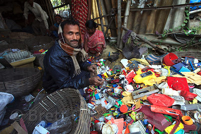 A worker disassembles plastic toys to reclaim the plastic for recycling, at a small recycling operation in the East Kolkata W...