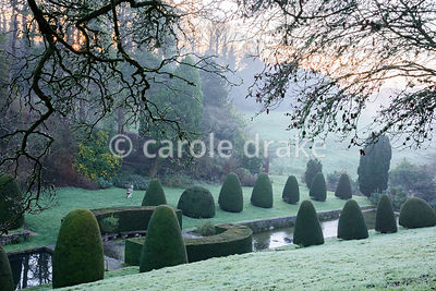View down to the frozen lily pond framed with clipped yews in the Canal Garden in winter at Mapperton, Dorset