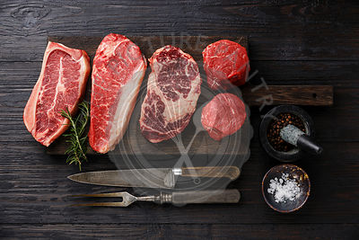 Variety of Raw Black Angus Prime meat steaks Blade on bone, Striploin, Rib eye, Tenderloin fillet mignon on wooden board