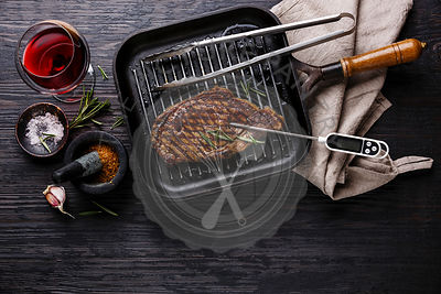 Grilled Steak Striploin on pan and meat thermometer on black burned wooden background copy space