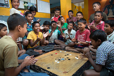 Children play carrom at a shelter in Calcutta, India