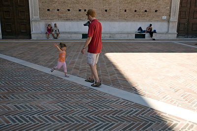 Italy - Urbino - A tourist videos his little girl outside the outside the Palazzo Ducale