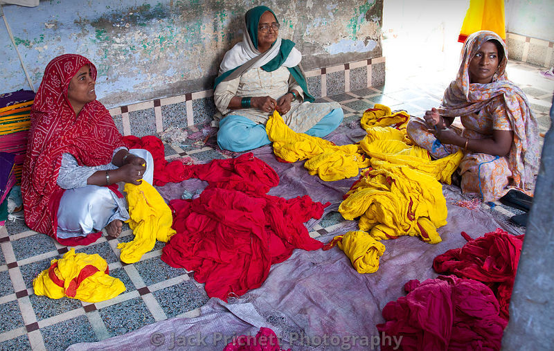Women sort and prepare dyed cloth.