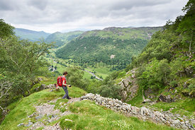 A hike walking down the narrow track at Little Stanger Gill, Bull Crag near Stonethwaite in the English Lake District.