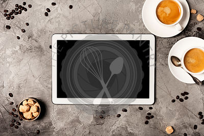 Tablet and coffee on grey stone background. Top view. Flat lay style.
