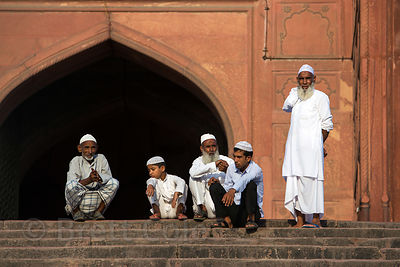 Muslim men and boys sit on the steps of the Jama Masjid mosque, Delhi, India