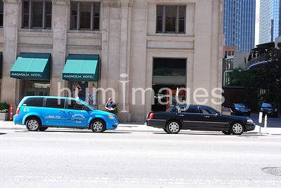 One taxi and one limo in front of a hotel in downtown Dallas, TX