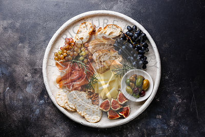 Italian snacks food with Ham, Olive, Cheese, Grapes, Sausage and Bread on dark background