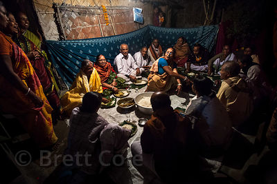 Krishna devotees eat dinner in a house in Chingrihata, Kolkata, India.