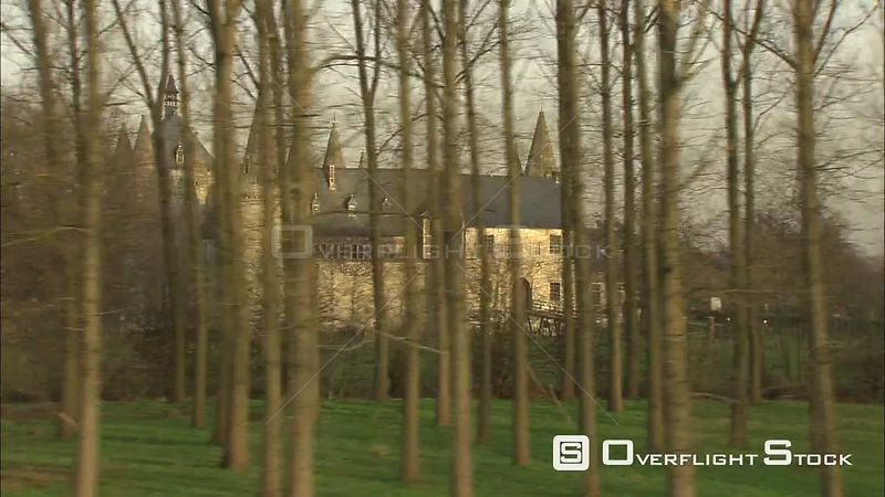 Past Castle of Laarne, partially screened by trees, to orbit for full view Laarne, Belgium