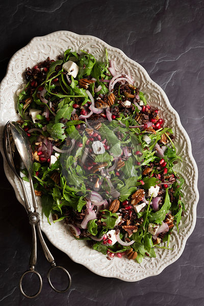 Rocket, pomegranate and black rice salad on an oval serving dish.