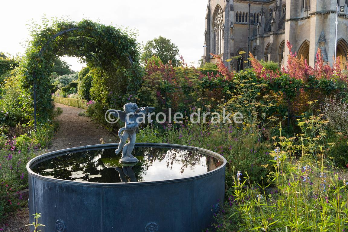 Lead fountain with putto and dolphin at the centre of the Organic Kitchen and Flower Garden, with apple tunnels shading the nearby paths, and the dramatic backdrop of Arundel Cathedral. Arundel Castle Gardens, Arundel, West Sussex, UK
