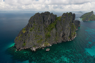 Aerial view of island with steep limestone cliffs,   birds' nests amongst the caves are highly protected or guarded for their...