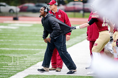 Coe College's Defensive Backs Coach Charles Watkins is held back by a Coe player as he makes calls to the field against Centr...