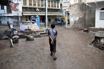 Boy walking in the rain in Pushkar, Rajasthan, India