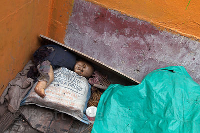 A baby doll sits disheveled in a garbage bin, like something from a scary movie, near Newmarket, Kolkata, India.