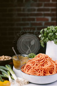 A big bowl of spiralized sweet potato noodles are photographed from the front view along with pad thai sauce, scallions, pean...