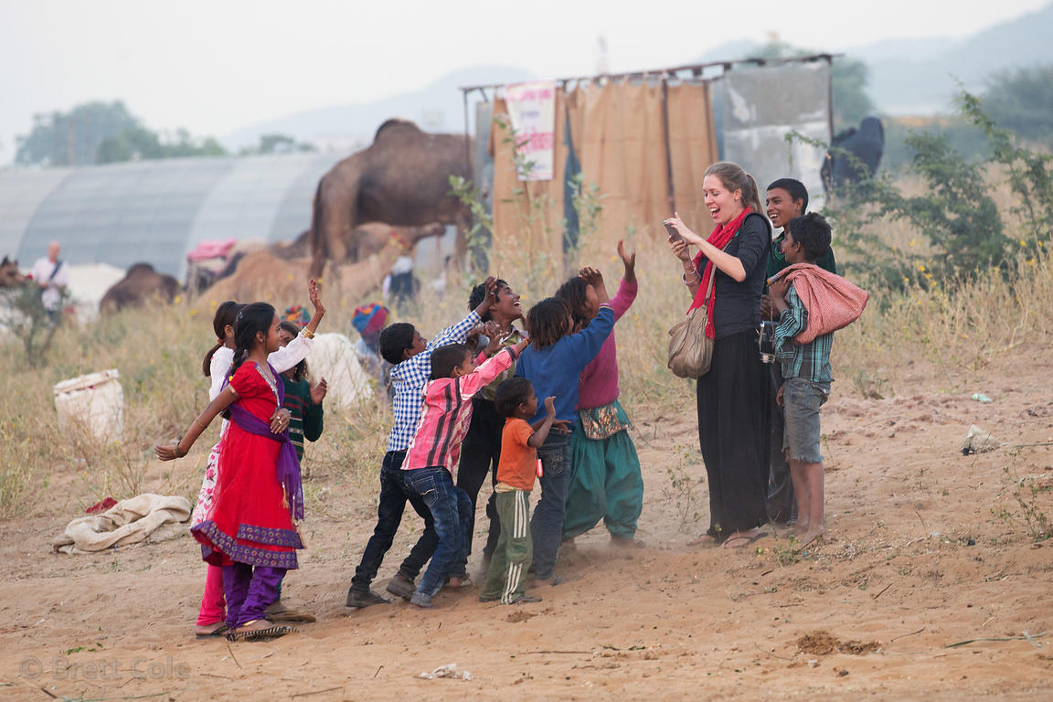 A foreign photographer is mobbed by enthuiastic children at the Pushkar Camel Fair, Pushkar, Rajasthan, India