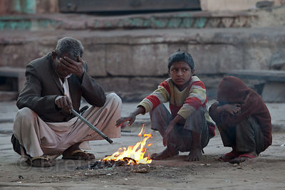 A man and two boys warm themselves at an early morning fire in the street, Jodhpur, Rajasthan, India