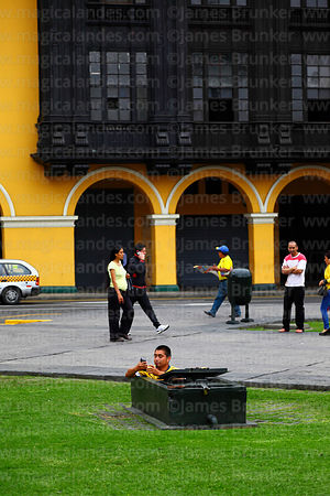 Maintenance worker taking photo with mobile phone from inside manhole cover, Plaza de Armas, , Lima, Peru
