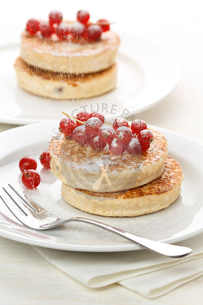 Delicious breakfast with pancakes and red currants on white background