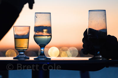 Lifestyle stock photo of a people drinkng wine and talking on a boat at night, Baltimore, Maryland