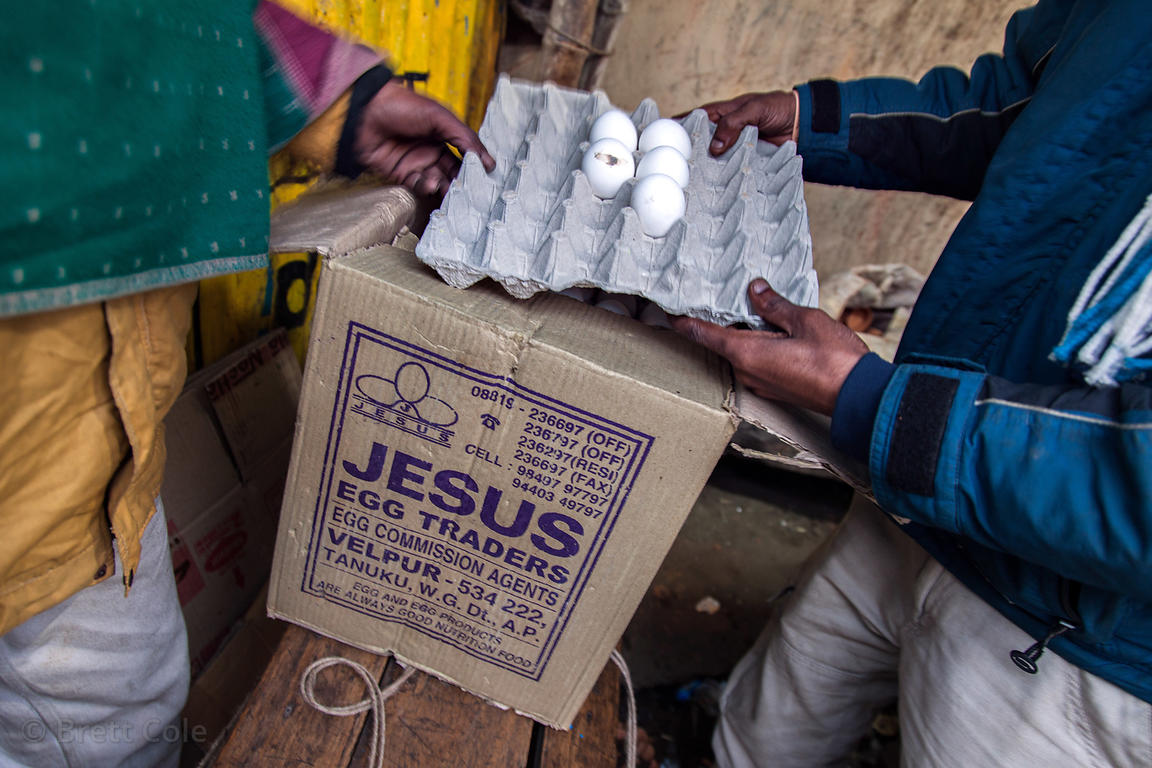 "A man unloads boxes of eggs labeled ""Jesus Egg Traders"" at a market in Chingrihata, Kolkata, India."