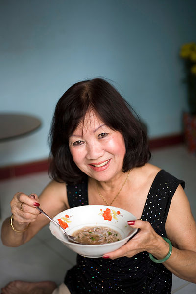 A woman breakfasts on a dish of Pho noodle soup