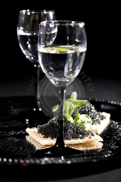 vodka and sandwiches with black caviar on black background