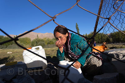 A woman drinks from a revered natural spring in Saboo village,  Ladakh, India