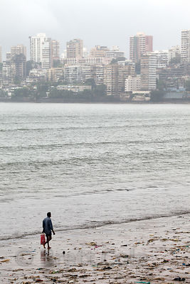 A man walks on Chowpatty Beach, Mumbai, India. In the background is Back Bay (Arabian Sea).