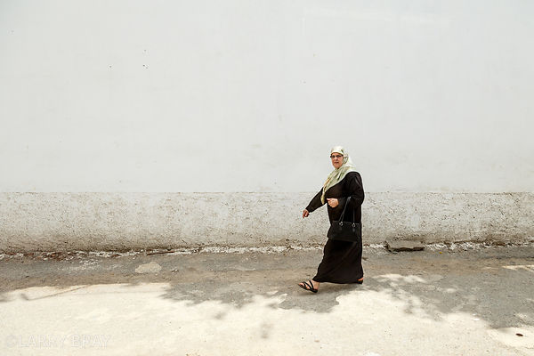 Lady walking past plain wall in Algiers, Algeria, North Africa