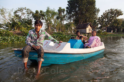 Children ride in a pedal boat on a small lake near the town of Chingrihata, East Kolkata Wetlands, Kolkata, India.