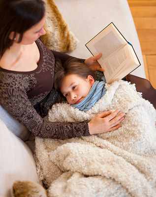 Mother reading to daughter on sofa